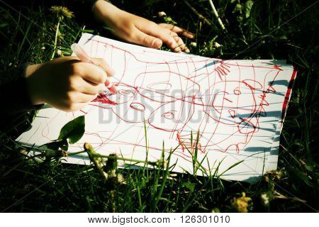 Close Up View Of Child's Hand Drawing Colorful Ornaments On Paper. Notebook In Fresh Green Grass Of
