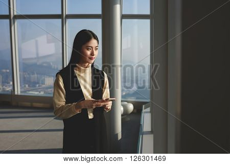 Young Japanese woman is waiting file download in e-mail letter on her mobile phone while is looking into big skyscraper window. Female proud CEO having work break while is standing in modern office
