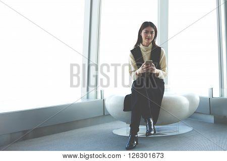 Japanese female worker of successful real estate company reading news in internet via mobile phone. Young asian student using cellular while sitting in modern office interior with contemporary design