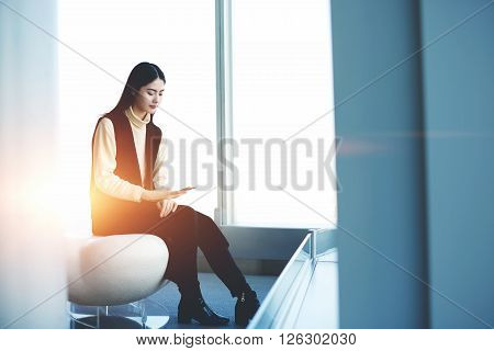 Japanese young woman proffesional of successful company is reading financial world news on smart phone application. Asian female student is sitting with cell telephone in high business school interior