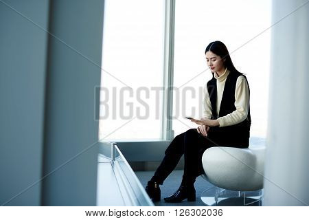 Asian woman skilled realtor is typing text message on mobile phone to customer what she is waiting him in luxurious apartment which he wants to rent. Concept of mobile connection and communication