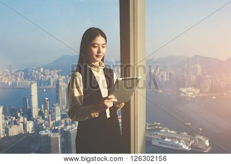 Young Asian woman worker of successful law firm is reading e-mail in internet via digital tablet from her client while is standing in modern interior against skyscraper window with New York city view