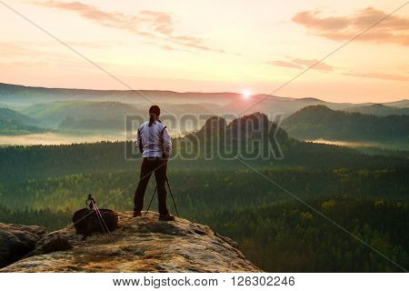 Professional Photographer In White Jacket  Takes Photos With Camera On Tripod On Rocky Peak. Dreamy