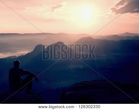 Tourist In Black Wind Jacket Sit On Sharp Rock And Watch Into Colorful Misty Valley Bellow. Sunny Sp