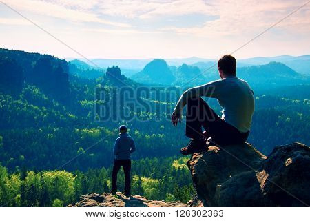 Boy and girl tourists stay on cliff and thinking. Dreamy fogy landscape blue misty sunrise in a beautiful valley below