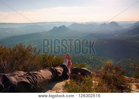 Long Tired Male Legs In Dark  Hiking Trousers Take A Rest On Peak Of Rock Above Valley.