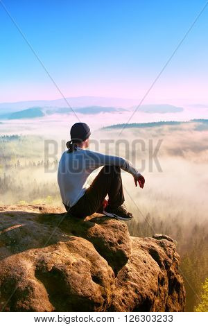 Adult Sportsman In White Shirt, Dark Trousars And Grey Cap. Man Sit On Sharp Cliff Above Valley In R
