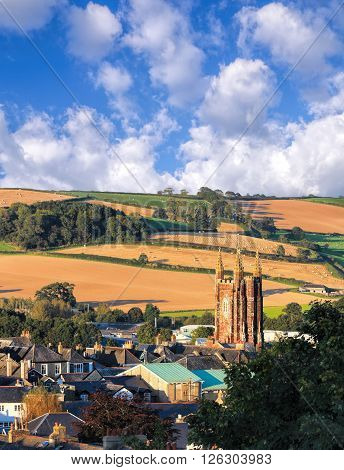Church in Totnes against countryside in England UK