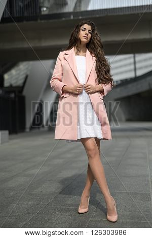 Cute girl stands with crossed legs on the background of the concrete building. She wears the white dress with dots and the pink coat and shoes. She looks into the camera and holds coat by her hands. Outdoors. Horizontal.