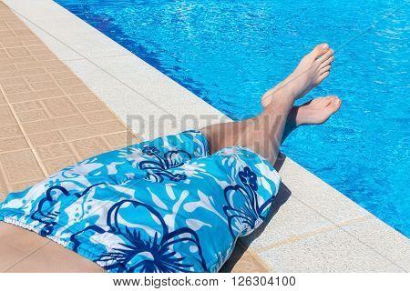 Teenage boy sunbathing at blue swimming pool on vacation in summer season
