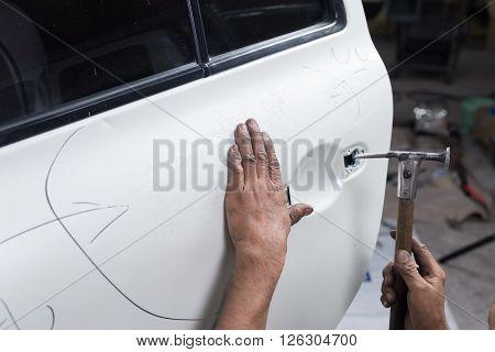 Auto body repair series : Mechanic fixing dented car door