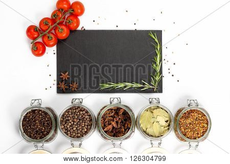 Spices and herbs in big glass jars. Food cuisine ingredients. Wooden board with anise rosemary. Cherry branch. Kitchen photography.