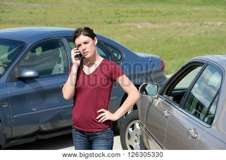 Young woman using cell phone after accident