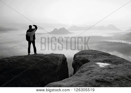 Moment of daybreak. Man on the rock empires and watch over the misty and foggy morning valley.
