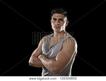 young attractive sport man with big and strong athletic body posing with folded arms wearing sweaty singlet looking cool and showing attitude isolated on black background