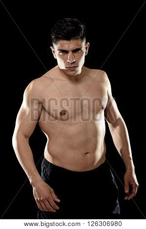 young handsome sport man posing with strong naked torso looking cool and defiant isolated on black background in healthy lifestyle and gym club bodybuilding advertising concept