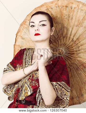 beautiful girl dressed as a geisha girl holding a Chinese umbrella. Geisha makeup and hair dressed in a kimono. The concept of traditional Japanese values.
