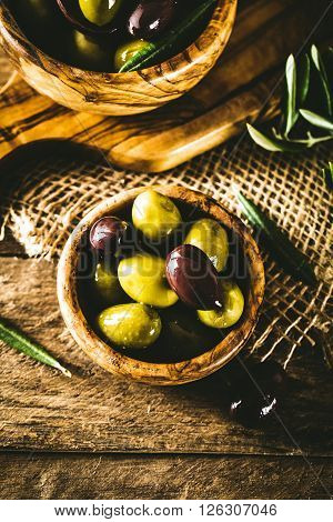 olives on olive branch. Wooden table with olives in bowl ** Note: Soft Focus at 100%, best at smaller sizes
