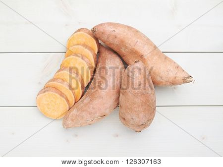 Sweet potato or Ipomoea batatas composition over the white wooden boards surface