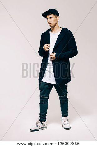 Cool fashion male model posing. Street youth fashion. Studio. Indoor.