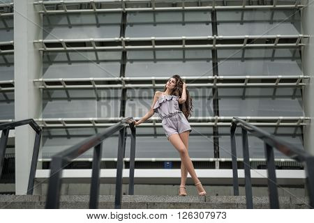 Stylish brunette with beautiful hair in the gray suit and beige sandals stands near stair on the background of the metal-glass constructions. She holds her right hand on the black hand-rail. She looks to the right and touches her hair by left hand. Outdoo