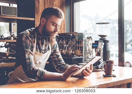 Technologies make business easier. Young bearded man in apron using his digital tablet while leaning on bar counter in coffee cafe.