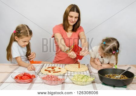Two Little Girls Enthusiastically Watched As Mum Pours Ketchup Basis For Pizza