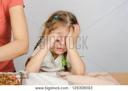 Little Girl Wearily Rubbing His Eyes At The Kitchen Table While Mom Cooks