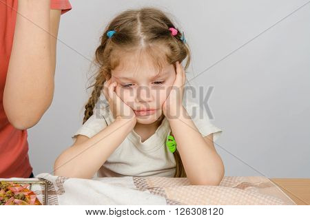 The Baby Girl With A Sad Expression On Her Face Sitting At The Kitchen Table