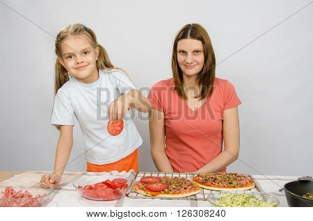 Six-year Girl Puts On The Pizza Tomatoes Under The Supervision Of Mum