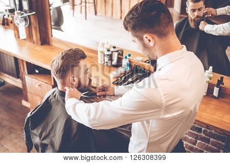Beard grooming. Top view of young bearded man getting beard haircut by hairdresser while sitting in chair at barbershop