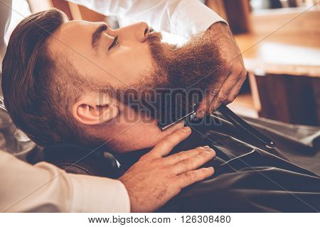 Sharp and dangerous. Close-up side view of young bearded man getting shaved with straight edge razor by hairdresser