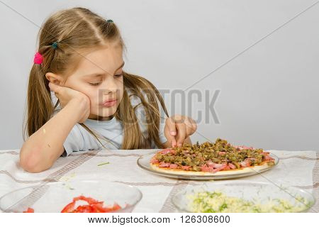 Little Six Year Old Girl Sitting At The Table And Picks Unfinished Pizza