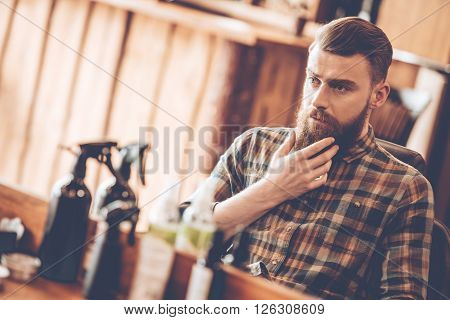 It is time for grooming. Handsome young bearded man looking at his reflection in the mirror and keeping hand on chin while sitting in chair at barbershop