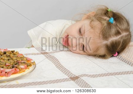 Little Girl With Protruding Tongue Rested Her Head On The Table And Looks At The Pizza