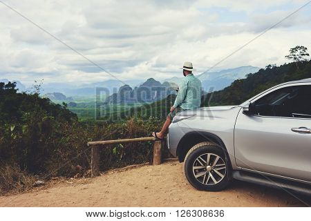 Young man wanderer is enjoying beautiful landscape during summer adventure on rental automobile in Asia. Male traveler is dreaming about something while is sitting on a car hood against Amazon view