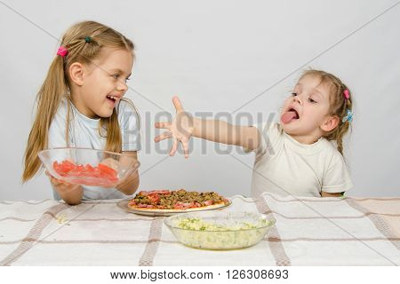 Two Little Girls At A Table Prepared Pizza. One With A Whimsical View Stretches A Hand To A Plate Wi