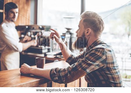 One more coffee please! Young handsome bearded man talking to barista while sitting at bar counter at cafe