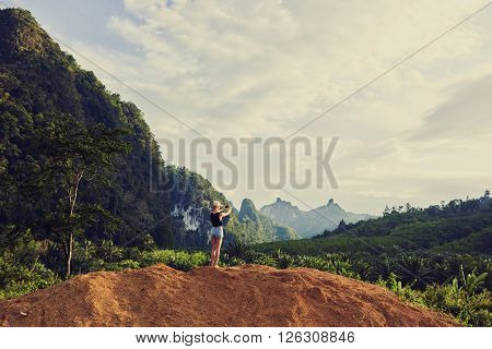 Back view of a woman is shooting video on cell telephone during summer vacation with daughter in Latin America. Female is taking photo with smart phone camera while is standing against jungle scenery