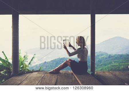 Back view of woman blog author is taking pictures on touch pad camera for travel website in network during adventure in Asia. Young hipster girl is shooting video with jungle scenery on digital tablet
