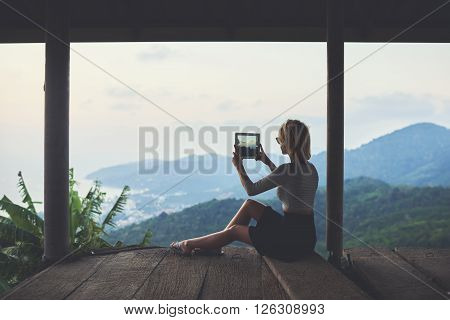Young female blog author is making photo on portable touch pad for her travel web page in social network. Woman is shooting video of wonderful view of subtropical forest during her travel in Thailand