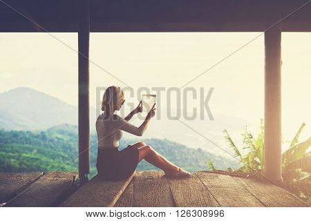 Woman tourist is taking photo with digital tablet camera of an amazing Amazon landscape from viewpoint. Young female wanderer is making pictures on touch pad during unforgettable trip in Latin America