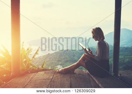 Female is typing something in diary on touch pad while is sitting against amazing Asian landscape in beautiful summer evening. Woman is watching video on digital tablet during her trip in Thailand