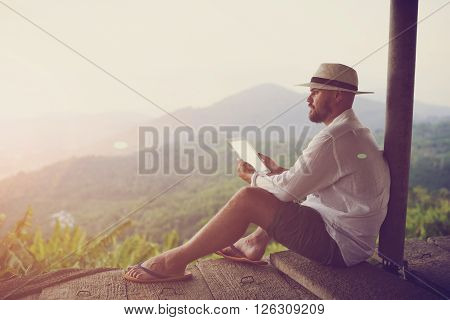 Young man tourist is dreaming about something good and holding digital tablet with copy space on the screen for your advertising text message. Man using touch pad during summer trip in Latin America