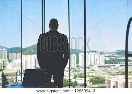 Back view of young man owner of a big successful the construction company is looking in window at houses that built workers on his project. Male financier is resting after meeting with professionals