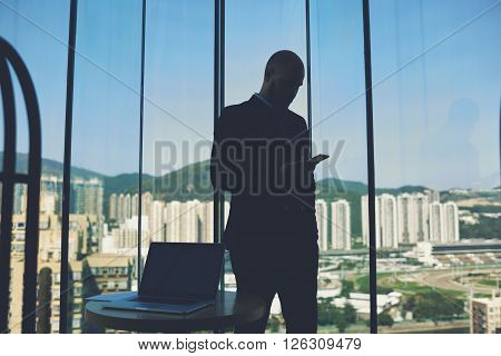Silhouette of a man is reading e-mail on mobile phone while is standing against office window with view of business center with tall buildings. Male manager is using cellphone after work on net-book