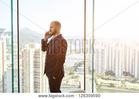 Young man managing director is having mobile phone conversation with client during break at job while is standing in his office near window with view of business district background with copy space