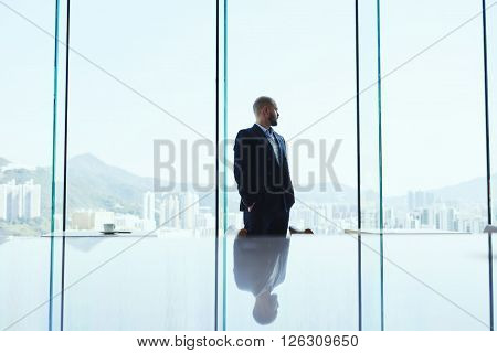 Serious man skilled financier is thinking about the crisis situations and methods of improving the situation while is standing in modern office interior and watching in window on business district