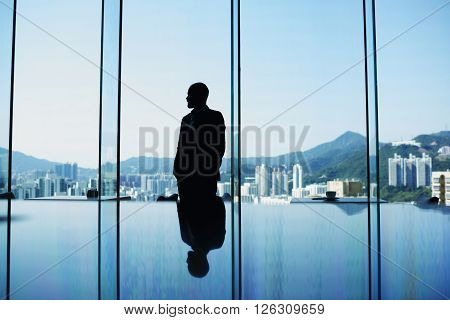 Silhouette of man skilled economist or businessman is standing in office interior near window with view of tall skyscrapers while is waiting important meeting with international partners. Copy space