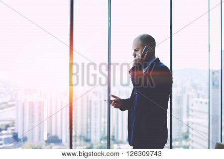 Serious man CEO dressed in suit having unpleasant mobile phone conversation while is standing near office window background with copy space for your advertising text message or promotional content
